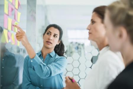 Three women brainstorming in meeting