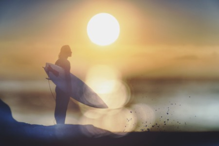 standing surfer surfboard looking out to sea sunset