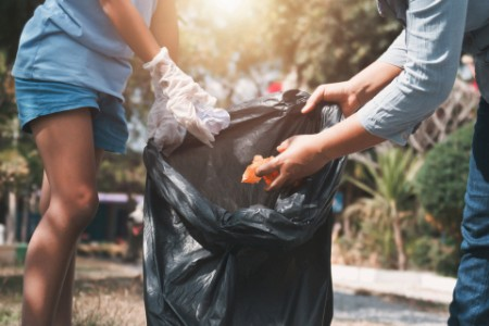 Mother and child help picking up trash at park