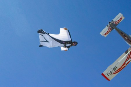 man in white wingsuit follows aircraft