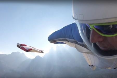 POV wingsuit pilot flying over mountains cliffs