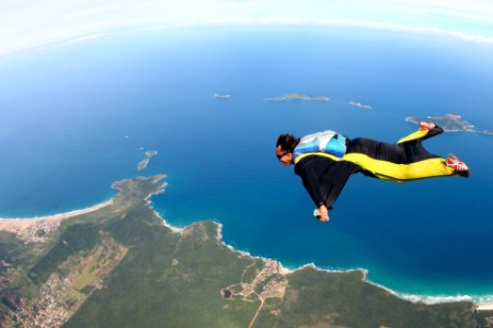 Black and yellow wingsuit flying over coastline