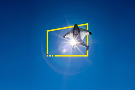 aerial view of flying white wingsuit with sunflare