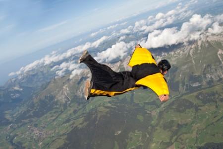 aerial view of wingsuiter flying through skies