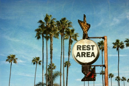 REST AREA rusty sign with palm trees and blue sky