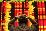 An investor reacts as he monitors the share index in a stock market gallery