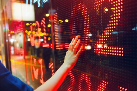 Womans hand on stock exchange market display screen showing stock drops in red