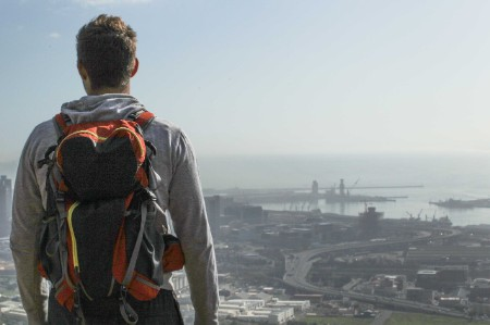 a young man with a hiking backpack overlooks the city of cape town from devils peak