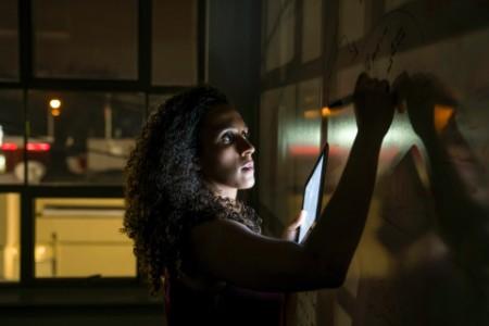 Businesswoman writing whiteboard tablet dark office