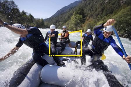 Grupo de hombres haciendo rafting en aguas bravas