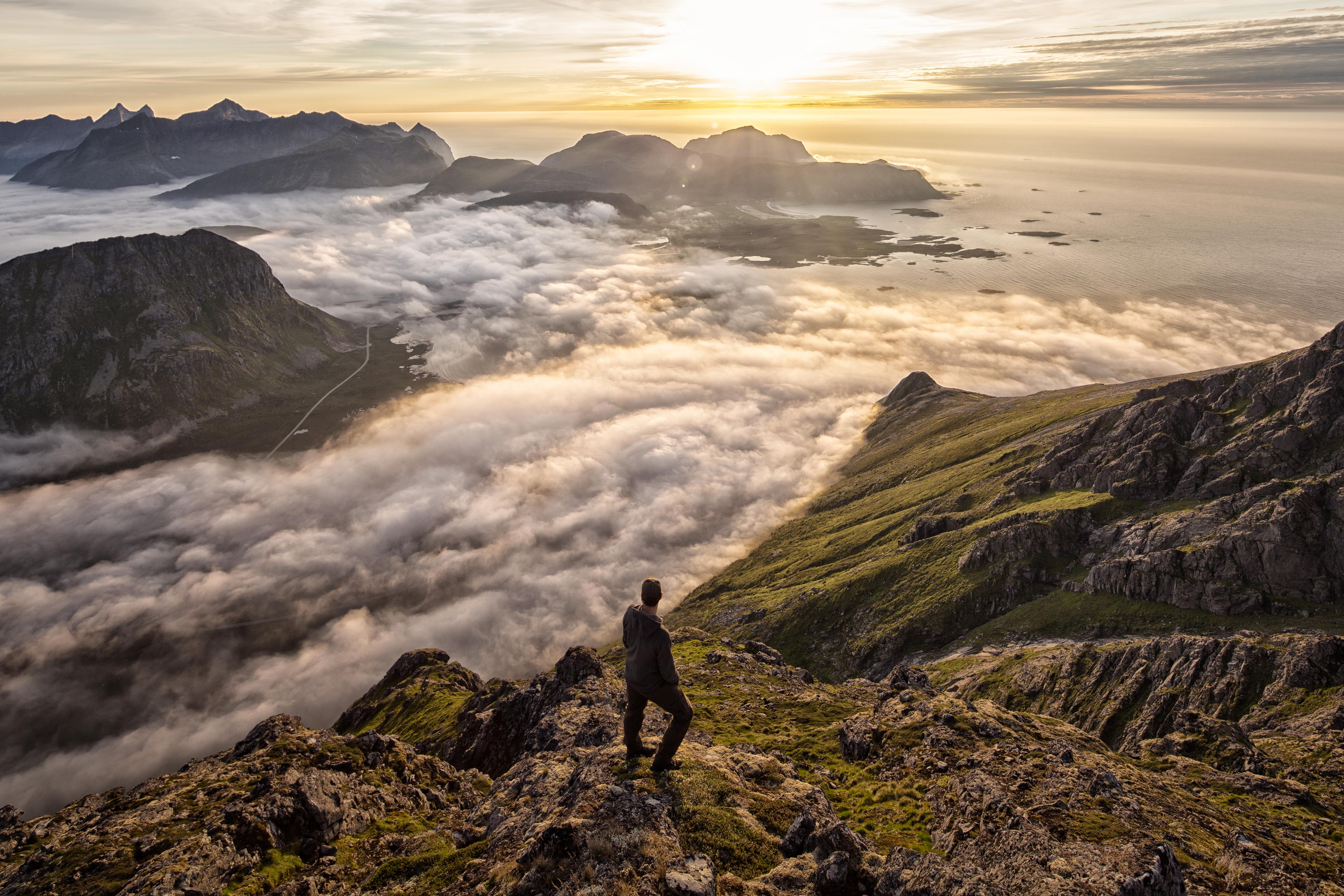 Man above the clouds on mountain Lofoten Norway