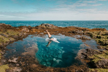 Man diving rock pool coast