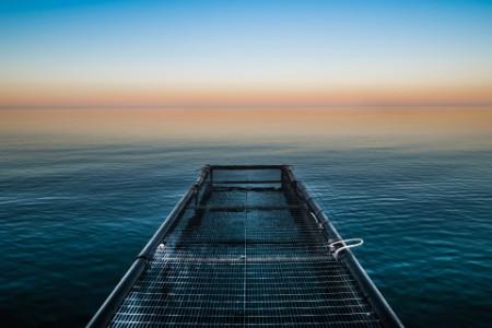 metal jetty calm sea sunset