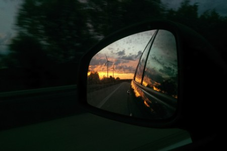 Reflection of wind turbines at sunset in car side mirror