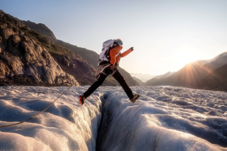 Woman jumping over crevasse.