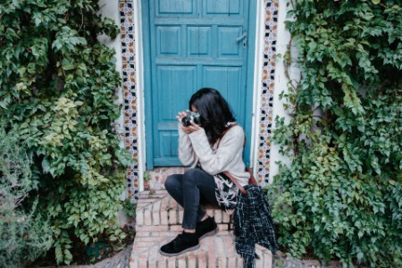 woman taking pictures sitting blue door