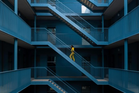 woman yellow tracksuit walking blue staircase building