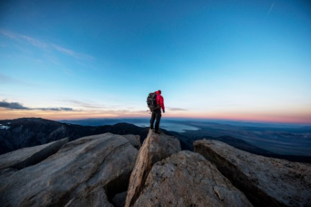 Mountain climber on the summit of a peak watching sunset