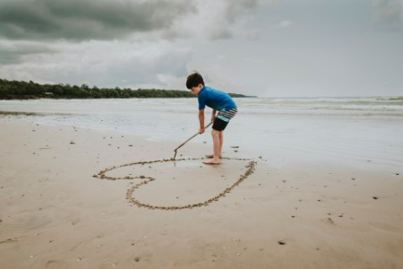 Boy making heart shape in sand at beach