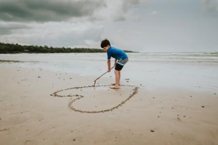 Niño haciendo forma de corazón en la arena de la playa