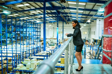 Business woman standing factory balcony
