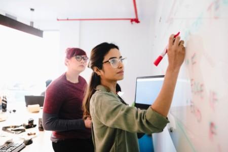 Brainstorming de mujeres empresarias en la pizarra de la oficina