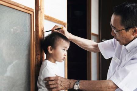 Abuelo grabando la altura del nieto en el pilar de la casa