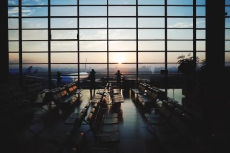 Gente viendo aviones en el aeropuerto saliendo de la sala de espera al atardecer