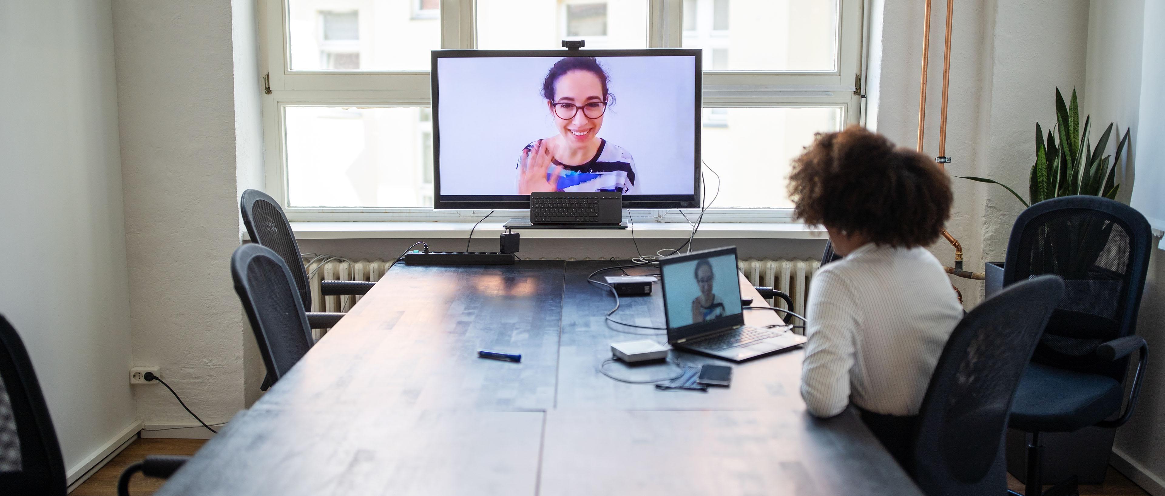 Mujer de negocios se reúne con sus compañeros de trabajo a través de una videollamada