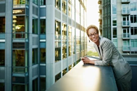 Mujer de negocios apoyada en un balcón sonriendo