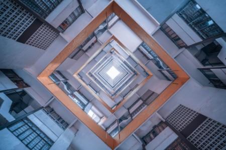 空を背景に近代的な建物を見上げるショット