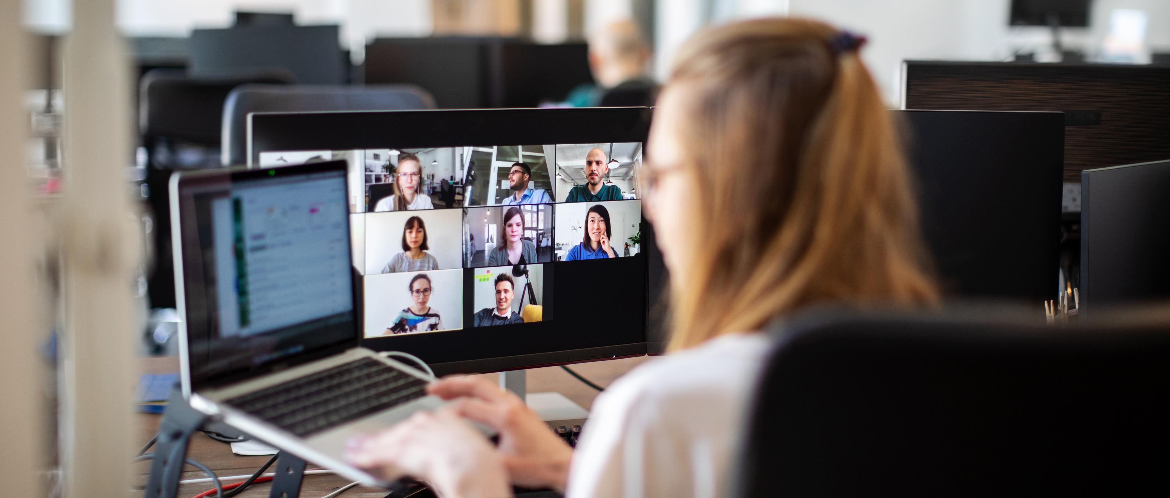 Mujer en videoconferencia con los miembros del equipo en la oficina