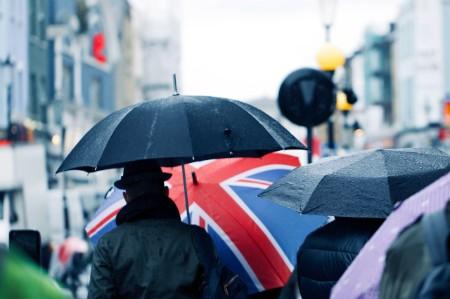 Man walking down busy street behind Union Jack umbrella