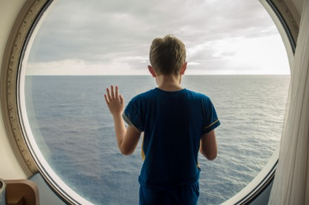 Jongen kijkt naar zee en lucht