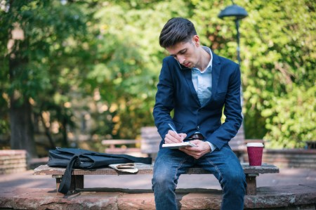 young man taking notes journal