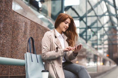 Business woman using smart phone city street