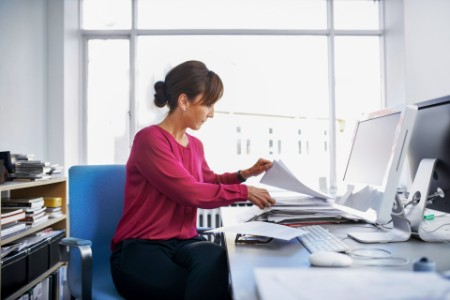 Businesswoman reviewing paper at her desk