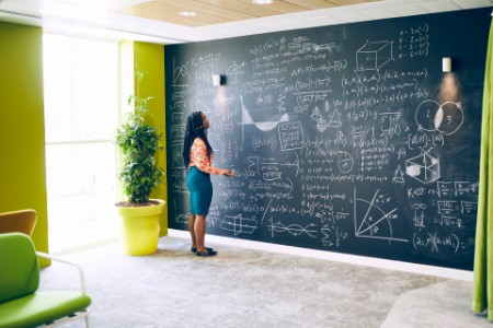 Businesswoman working with formula on wall
