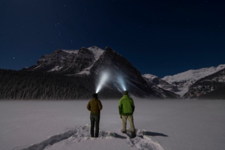 Couple stand in snowy clearing with headlamps
