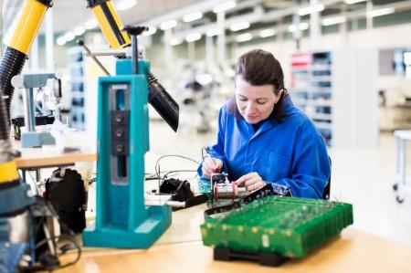 Una electricista que trabaja en una placa de circuito impreso