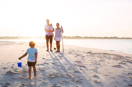 Family standing on beach against sky on sunny day