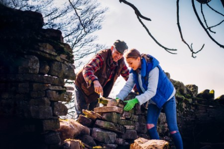 Farmer and Daughter Repairing an Old Stone Wall