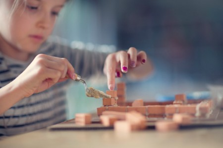 Girl building miniature house bricks