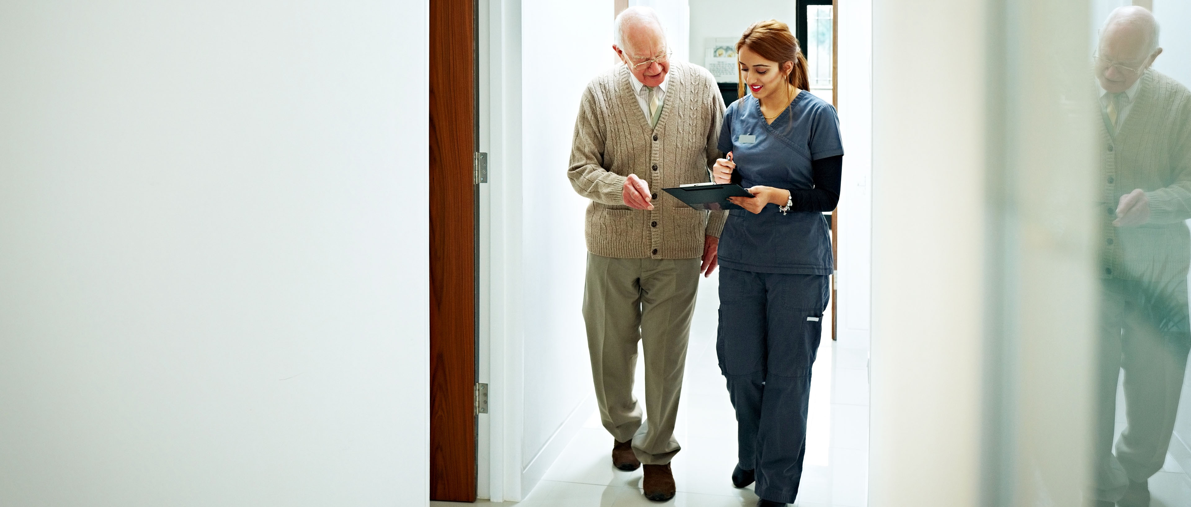 Nurse sharing medical report with senior patient