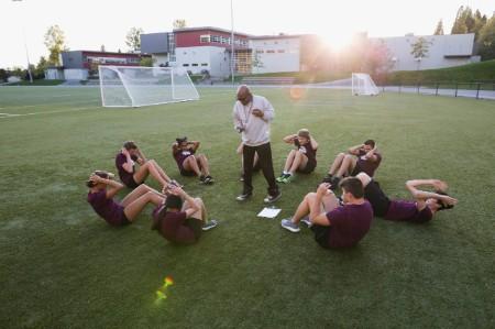 Leraar lichamelijke opvoeding laat leerlingen sit-ups doen