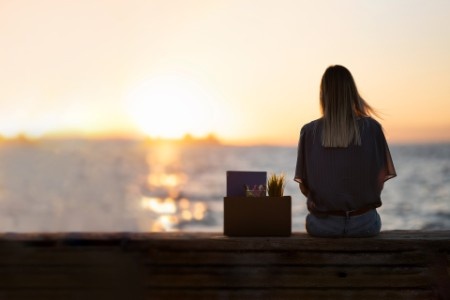 young woman sits by waters edge