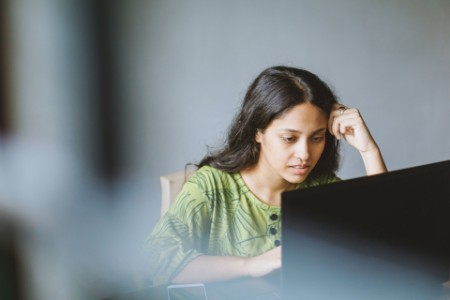 Young Indian woman using laptop in her workspace