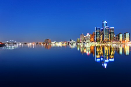 A wide night time shot of the city of Detroit reflected in the river