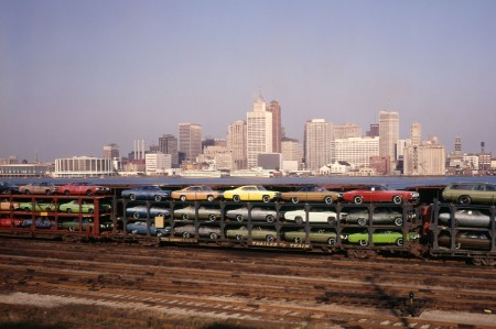 Cars sit on train transport wagons in the 1970s in front of the Detroit city skyline.