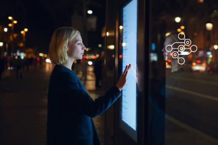 Frau interagiert mit digitalem Plakat